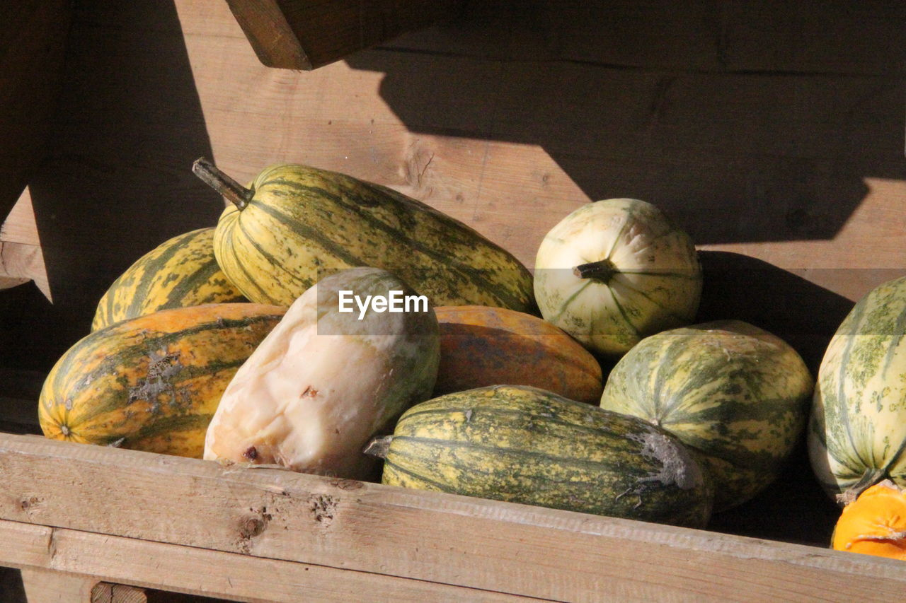 food and drink, freshness, food, healthy eating, wellbeing, vegetable, container, day, no people, pumpkin, still life, sunlight, market, box, shadow, crate, large group of objects, retail, nature, wood - material, outdoors