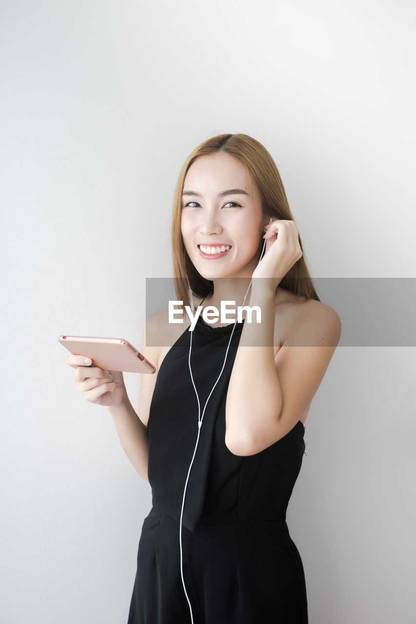 smiling, one person, young women, young adult, technology, beautiful woman, beauty, studio shot, happiness, white background, connection, indoors, standing, front view, portrait, three quarter length, wireless technology, holding, looking at camera, cut out, hairstyle