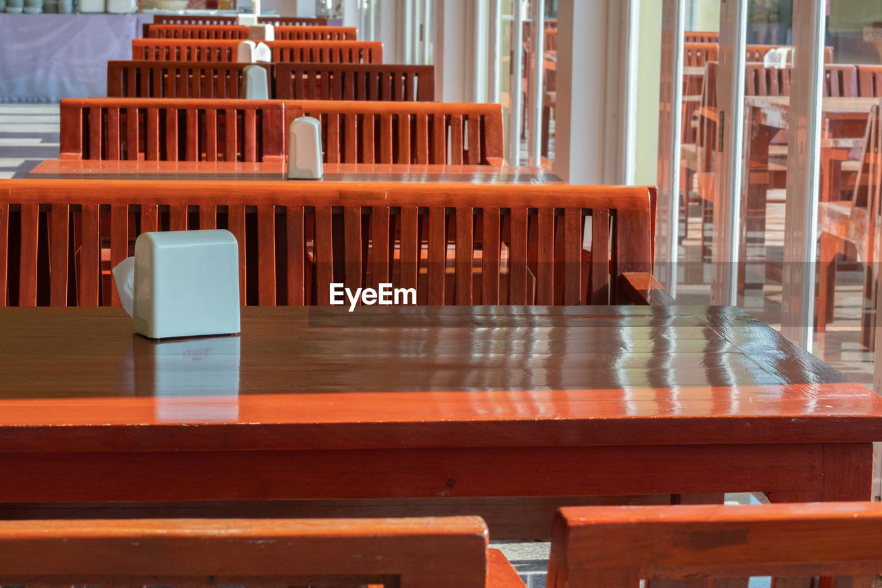 seat, table, chair, wood - material, no people, absence, empty, restaurant, architecture, day, furniture, business, cafe, arrangement, red, orange color, outdoors, building, reflection, setting, coffee table