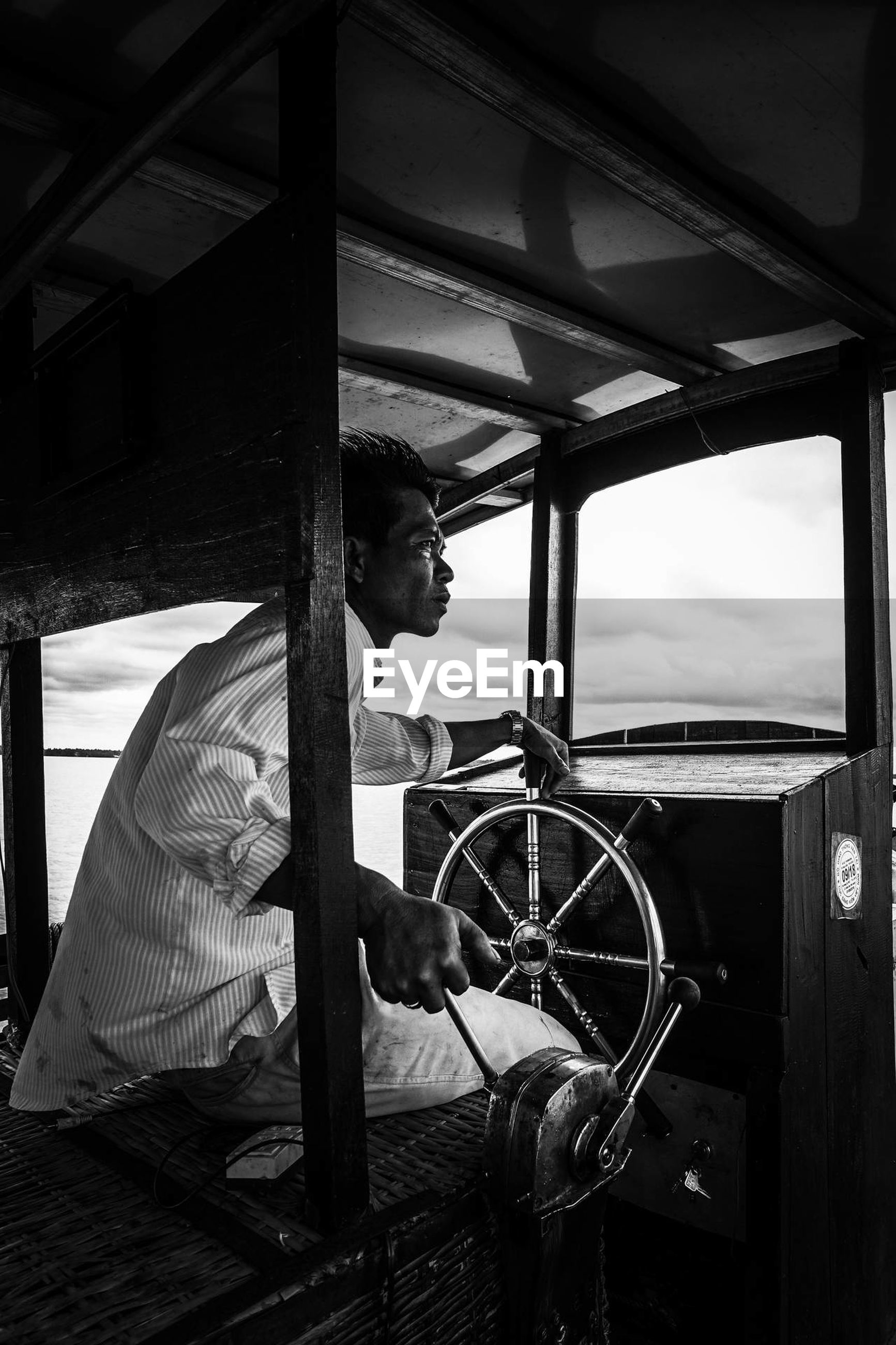 one person, real people, transportation, sitting, mode of transportation, indoors, day, lifestyles, working, window, young adult, nautical vessel, nature, men, vehicle interior, looking, side view, adult, wheel