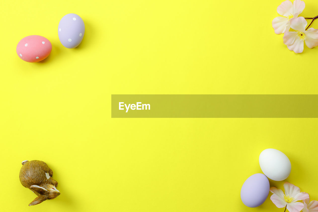 Directly Above View Of Easter Eggs With Flower Over Yellow Background