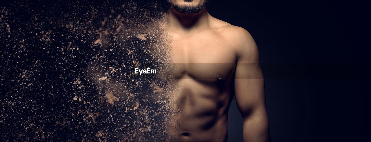 Digital composite image of shirtless man standing against black background