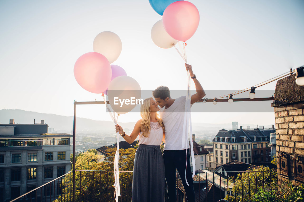 Couple Standing With Balloons Against Sky