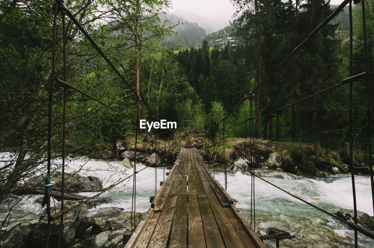 Footbridge over river against trees