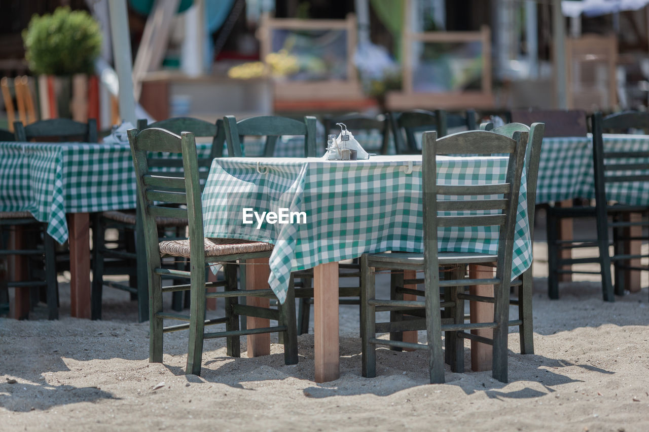 Empty chairs and tables at beach
