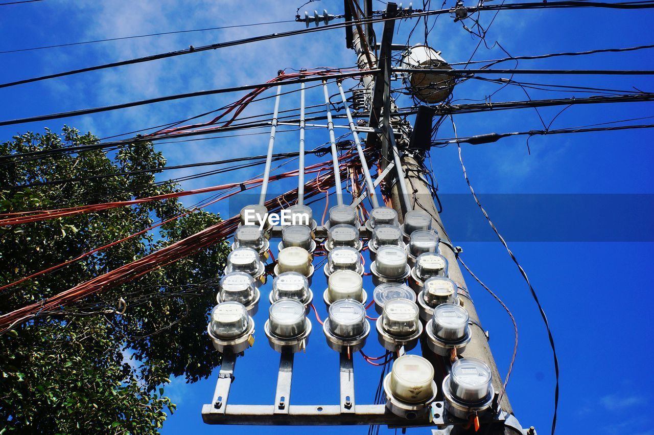 Low angle view of gauges on electricity pylon against sky