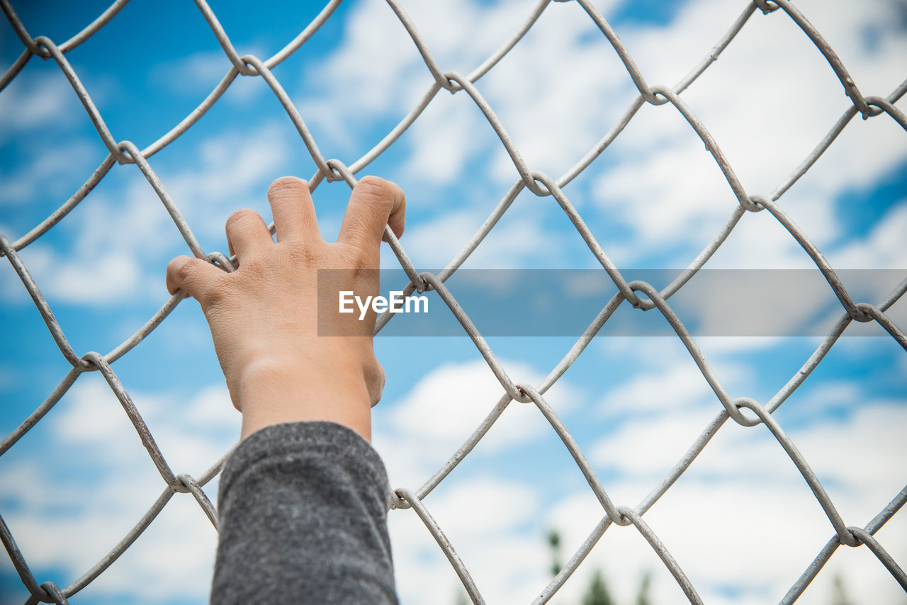 Cropped Hand Holding Chainlink Fence Against Sky