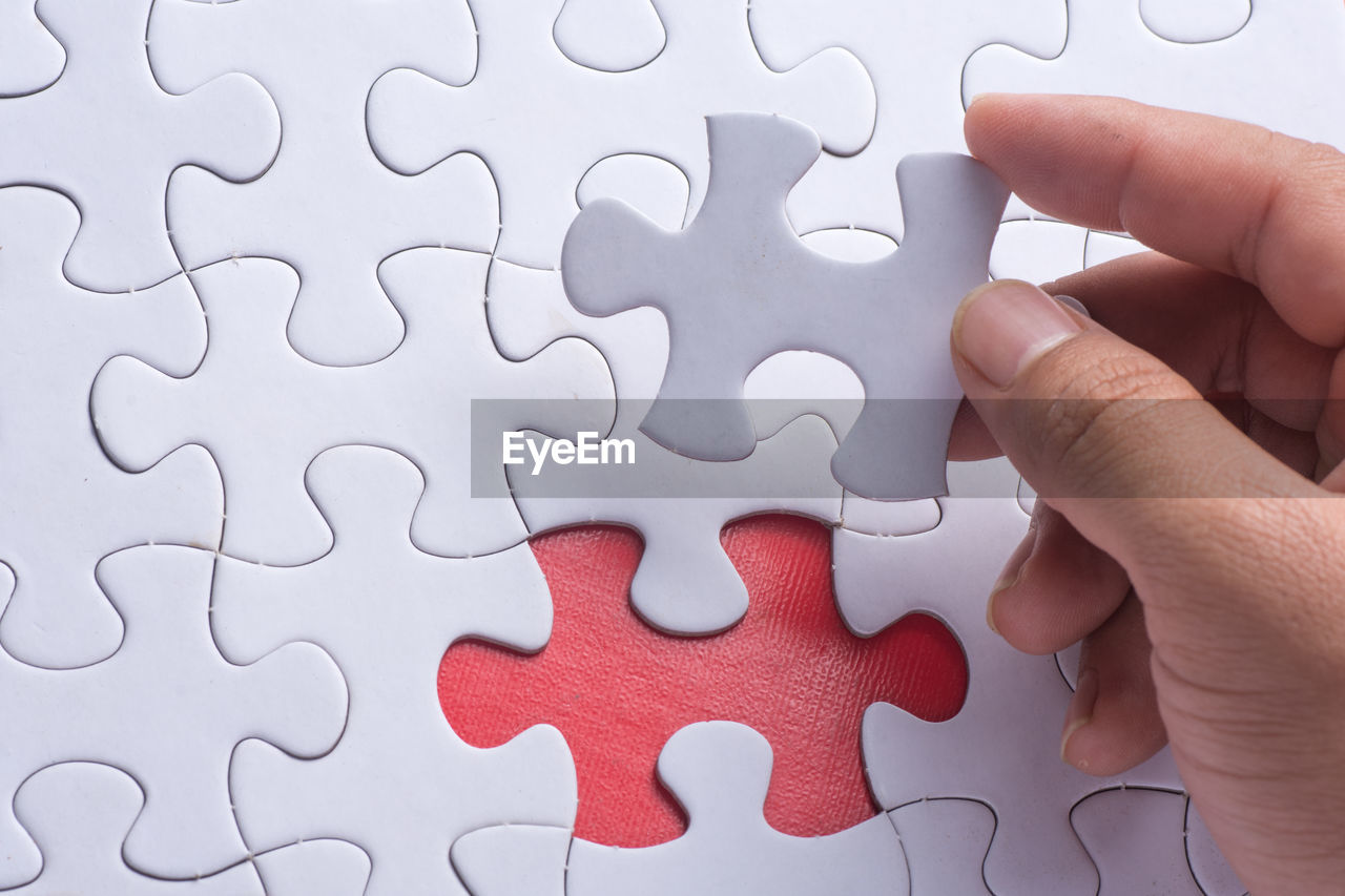 Close-Up Of Human Hand Holding Puzzle Piece