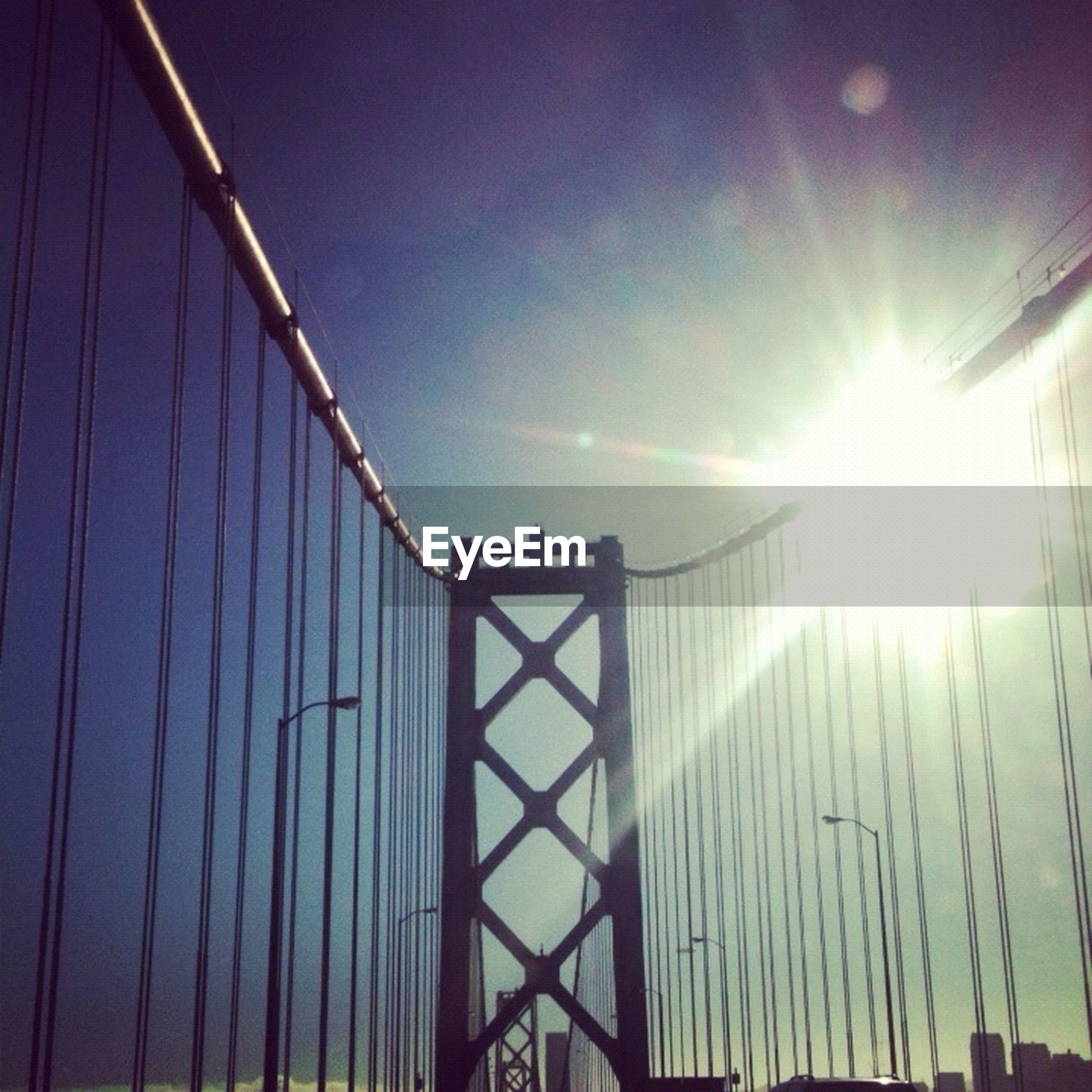sun, built structure, low angle view, lens flare, architecture, silhouette, sky, sunset, sunbeam, connection, sunlight, bridge - man made structure, clear sky, suspension bridge, outdoors, engineering, street light, transportation, dusk, crane - construction machinery
