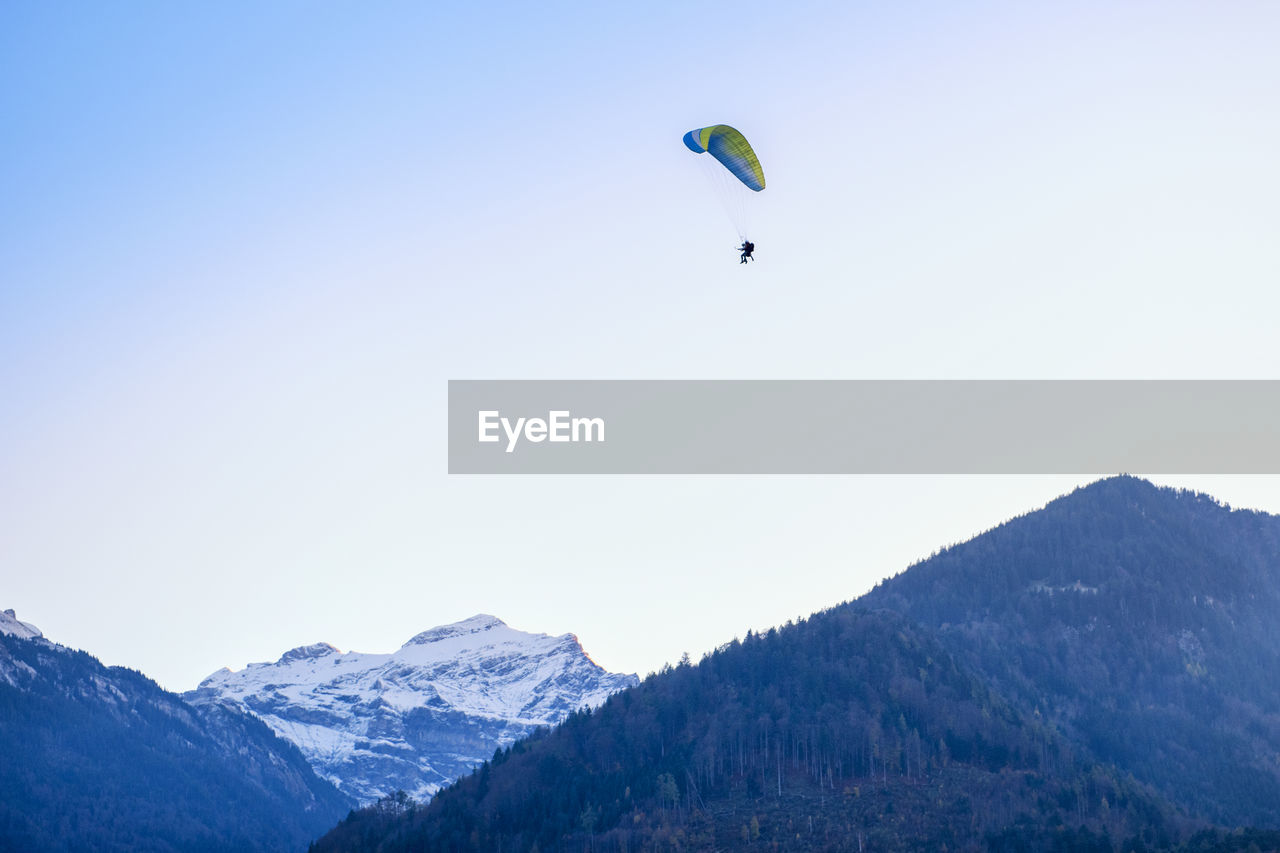 Low Angle View Of Person Paragliding Over Mountains Against Sky