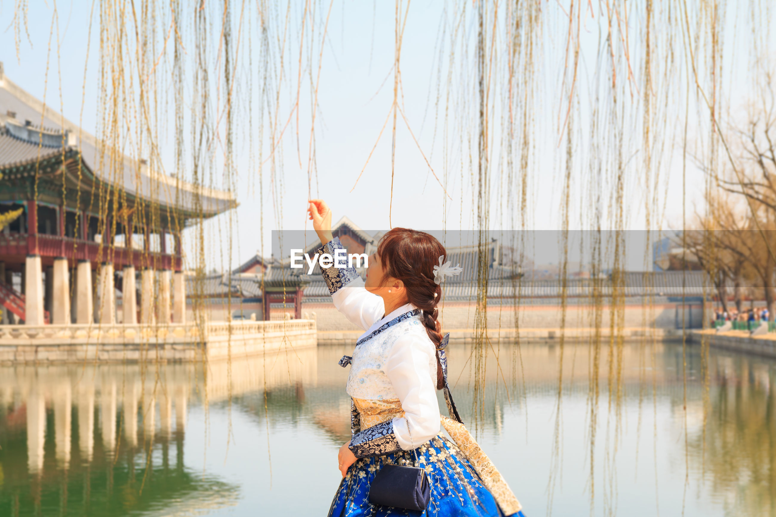 Young woman touching vines over pond against sky