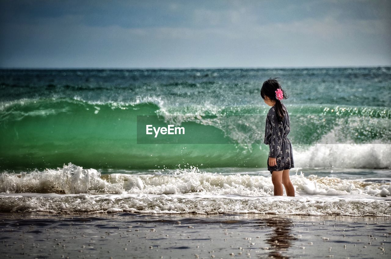 Girl Standing In Sea Against Sky On Sunny Day