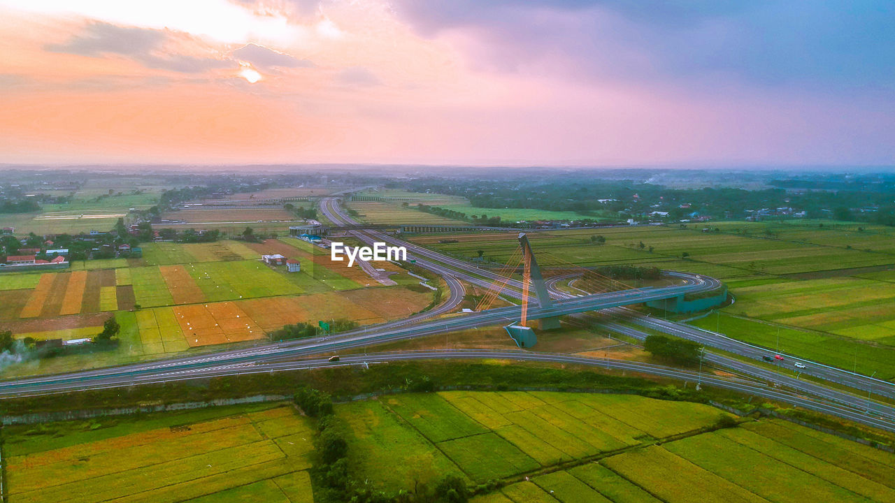 sky, landscape, cloud - sky, environment, transportation, nature, aerial view, scenics - nature, road, airplane, air vehicle, sunset, rural scene, no people, outdoors, beauty in nature, field, land, agriculture, mode of transportation