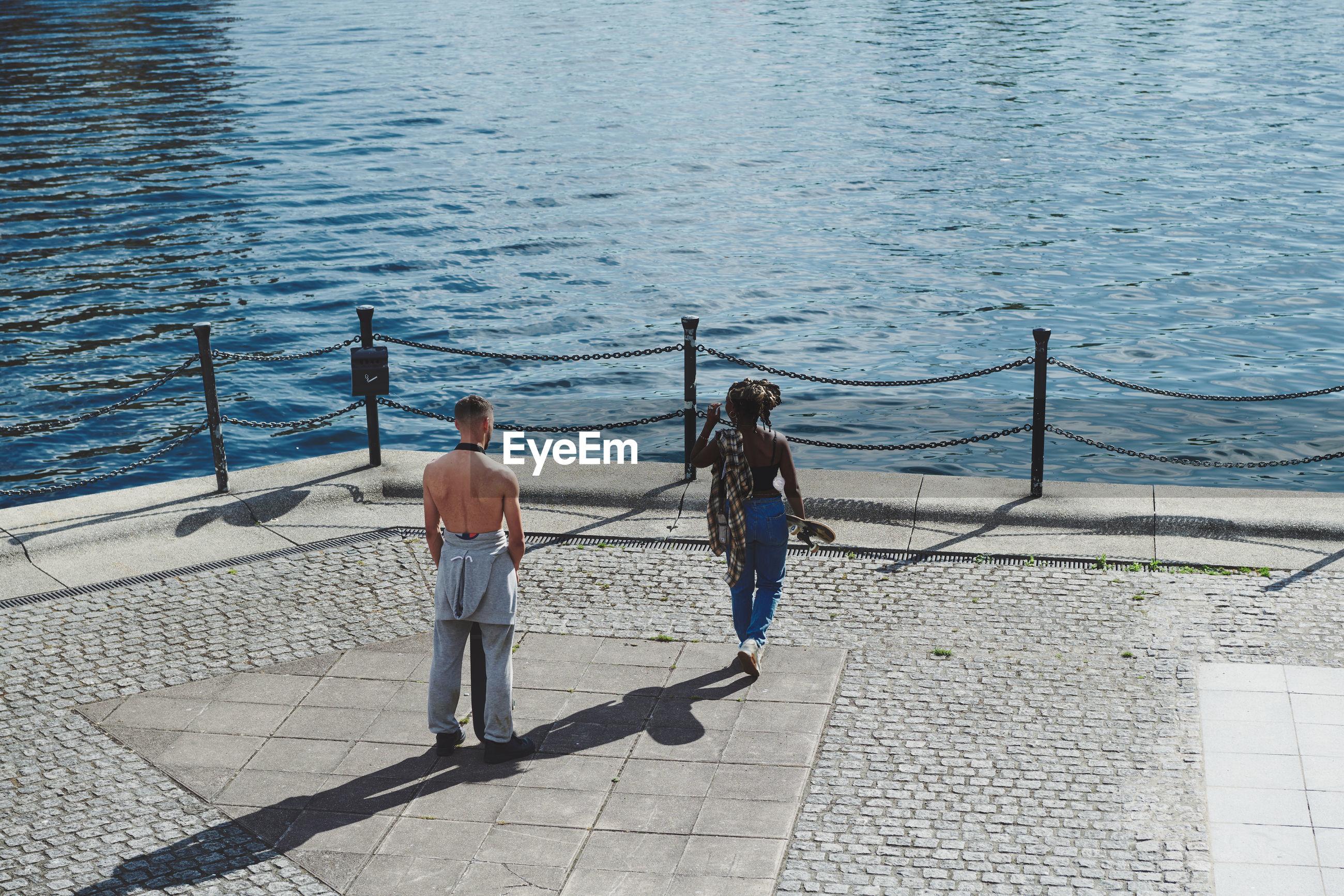 REAR VIEW OF MAN WALKING ON FOOTPATH BY SEA