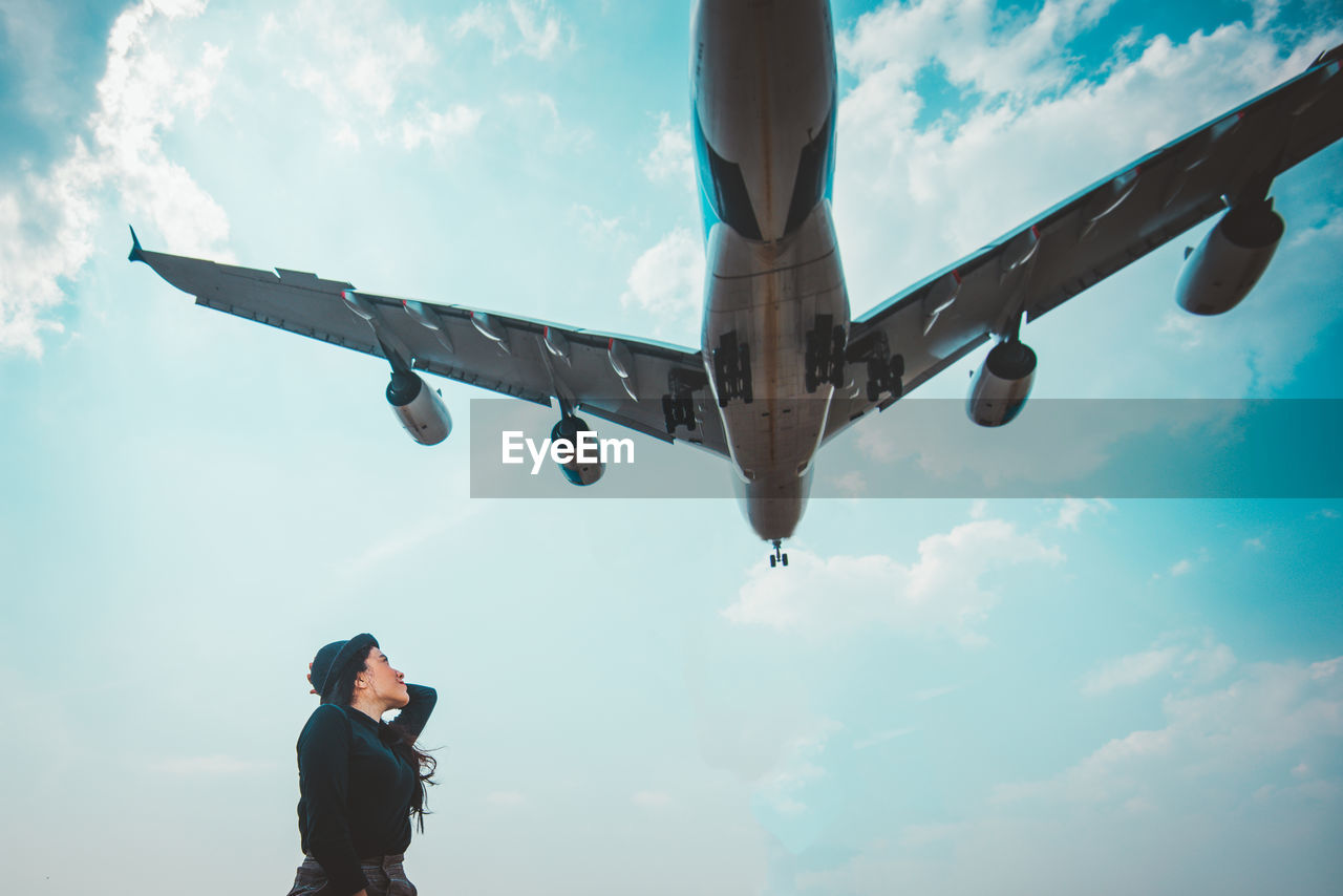 sky, cloud - sky, flying, low angle view, airplane, real people, air vehicle, nature, transportation, mode of transportation, mid-air, day, one person, lifestyles, men, travel, outdoors, public transportation, leisure activity, aerospace industry, human arm