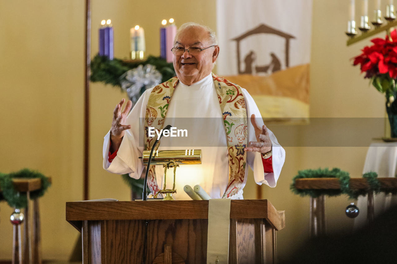 Smiling Priest Giving Speech In Church