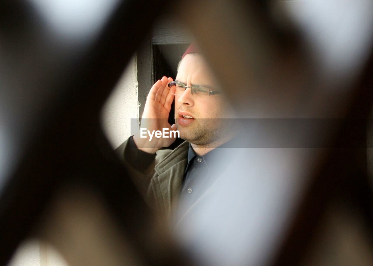 Muslim man calling for prayer in mosque seen through fence