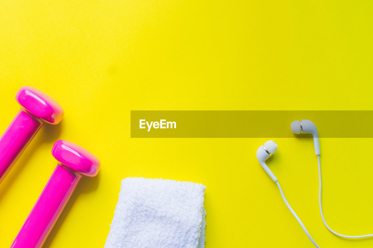 Directly above shot of pink dumbbells by towel in-ear headphones on yellow background