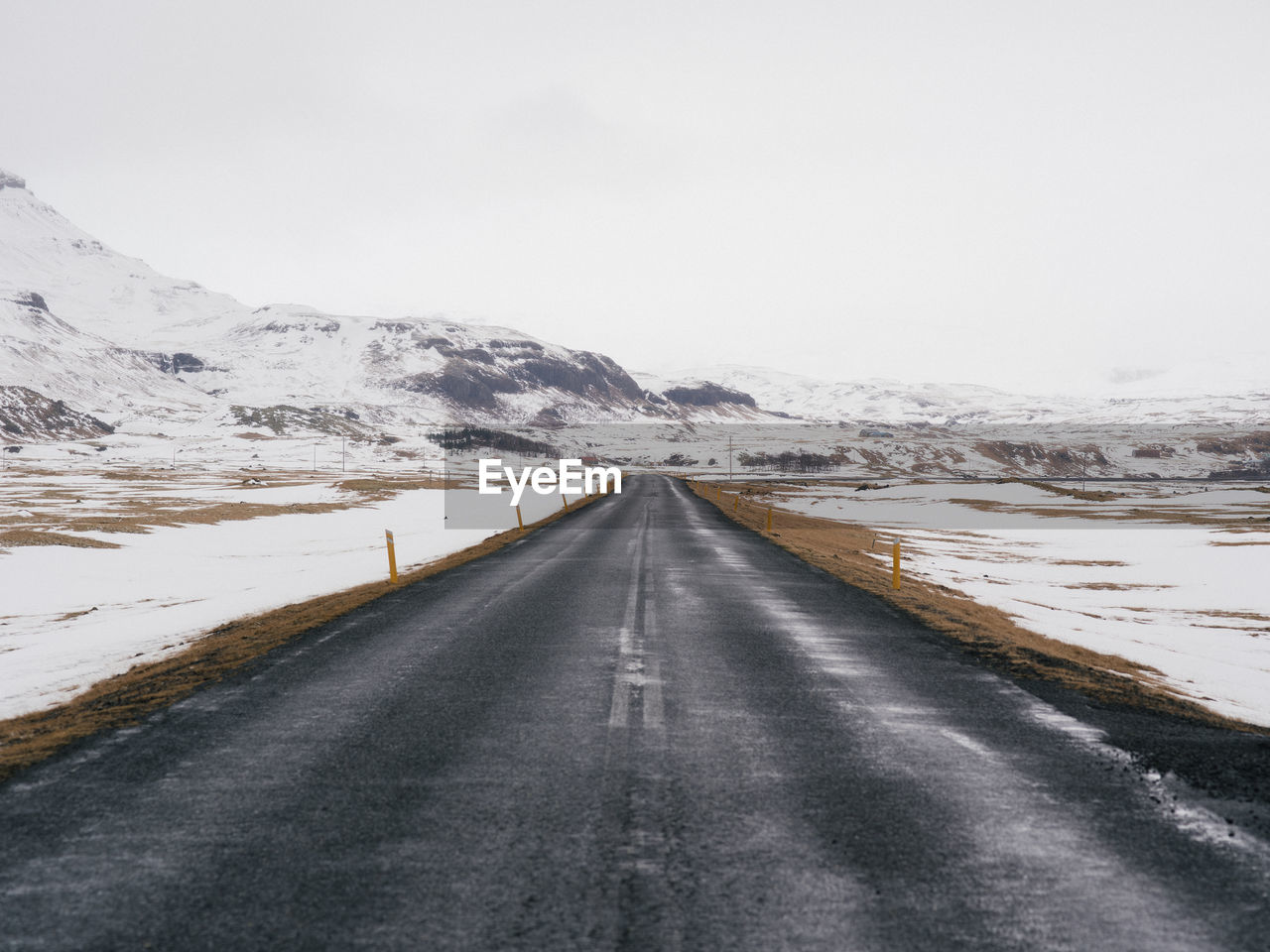 road, direction, the way forward, transportation, cold temperature, snow, winter, diminishing perspective, sky, mountain, scenics - nature, sign, vanishing point, nature, no people, beauty in nature, landscape, non-urban scene, environment, outdoors, snowcapped mountain, dividing line