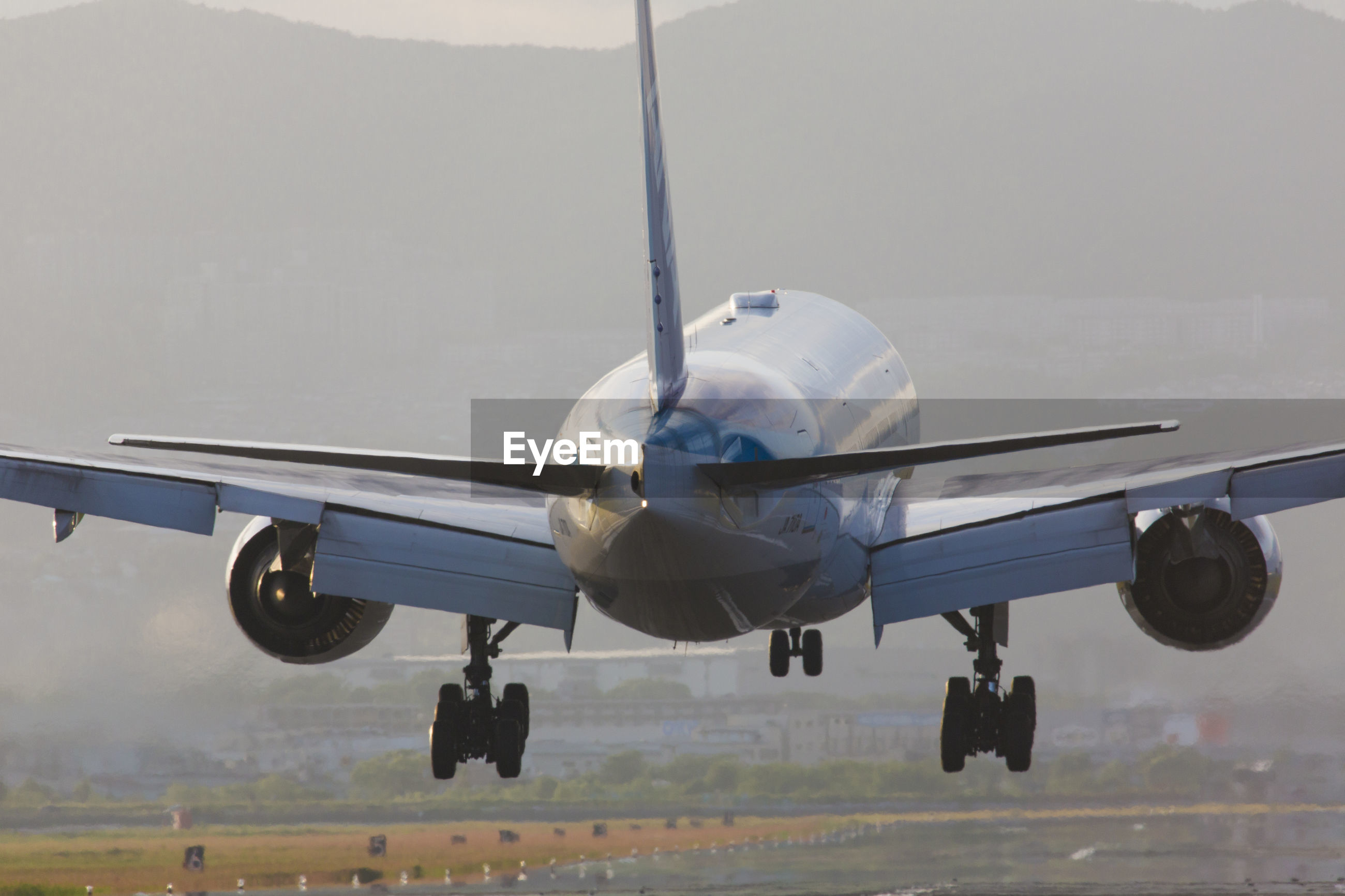 AIRPLANE FLYING OVER AIRPORT AGAINST SKY