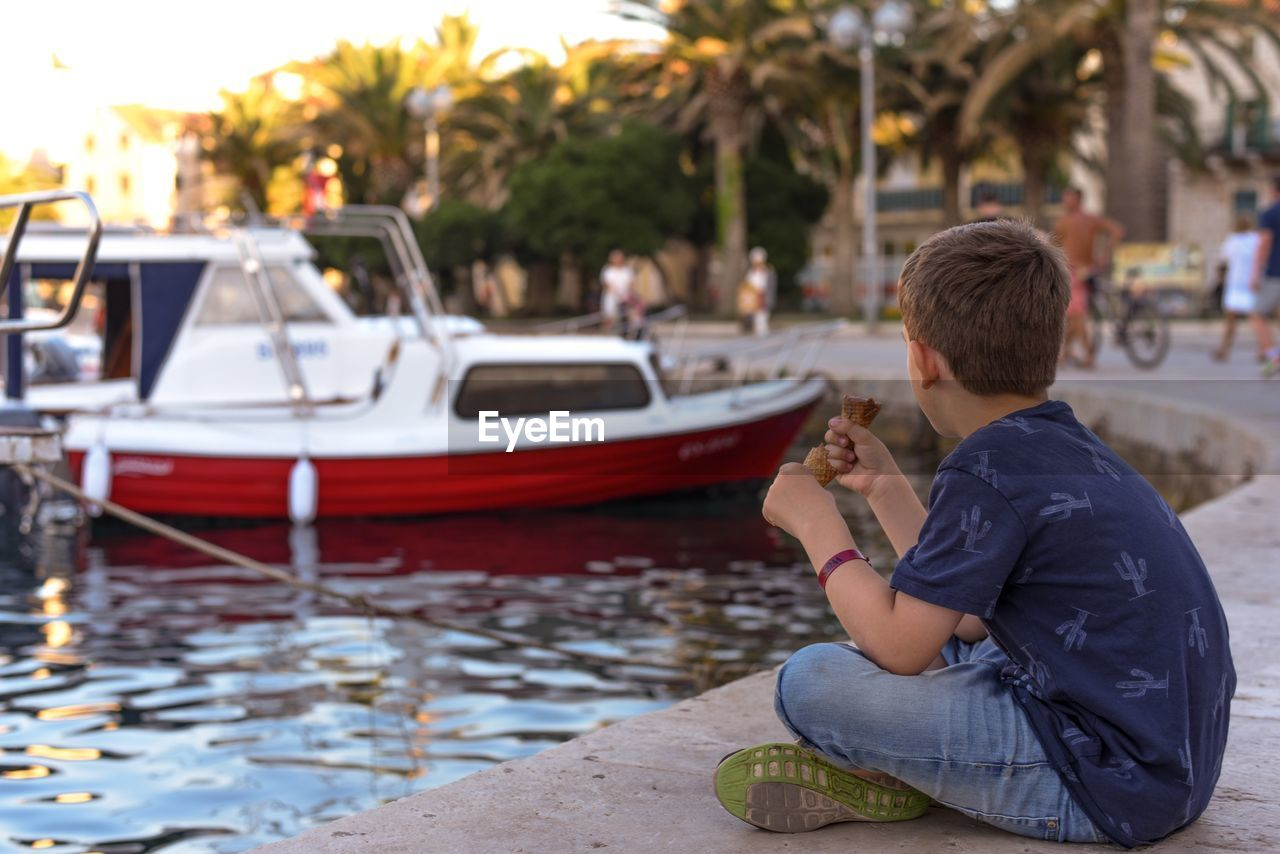 transportation, mode of transportation, real people, sitting, water, nautical vessel, leisure activity, one person, men, lifestyles, focus on foreground, casual clothing, nature, young adult, tree, city, young men, three quarter length, outdoors