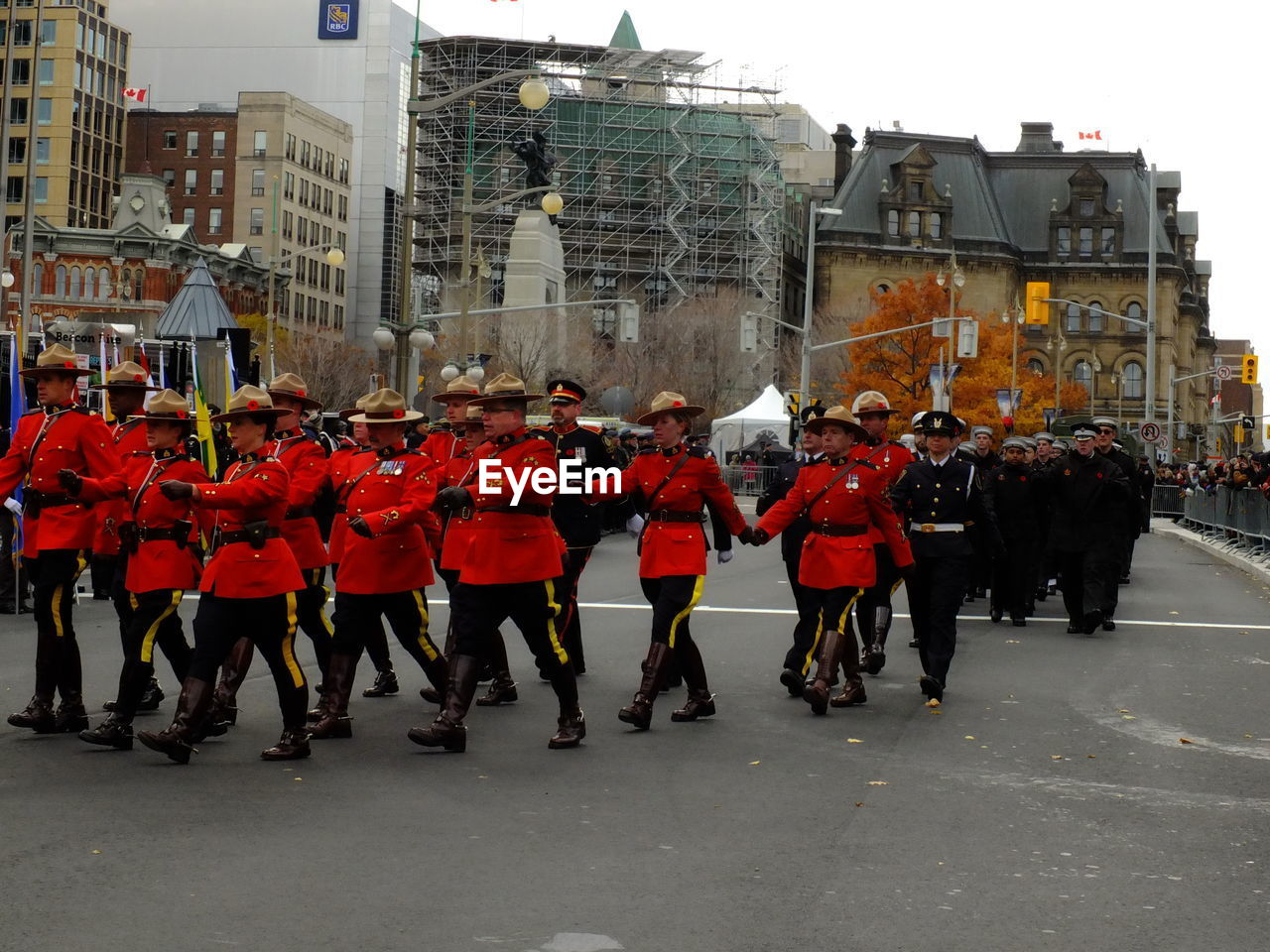 large group of people, building exterior, uniform, built structure, architecture, marching, men, real people, parade, rear view, military uniform, celebration, day, city, togetherness, military parade, outdoors, adult, people