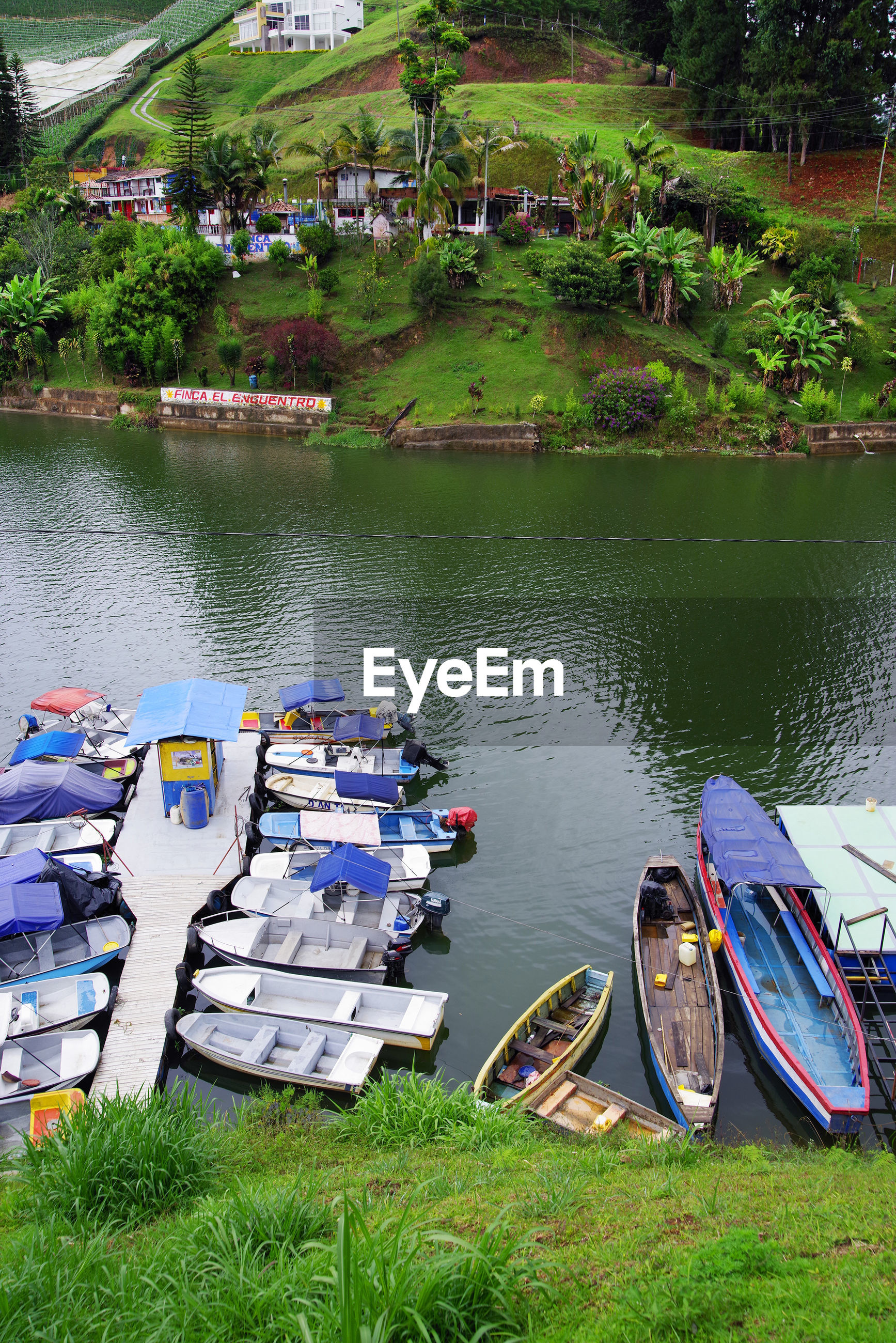 HIGH ANGLE VIEW OF BOATS MOORED BY LAKE