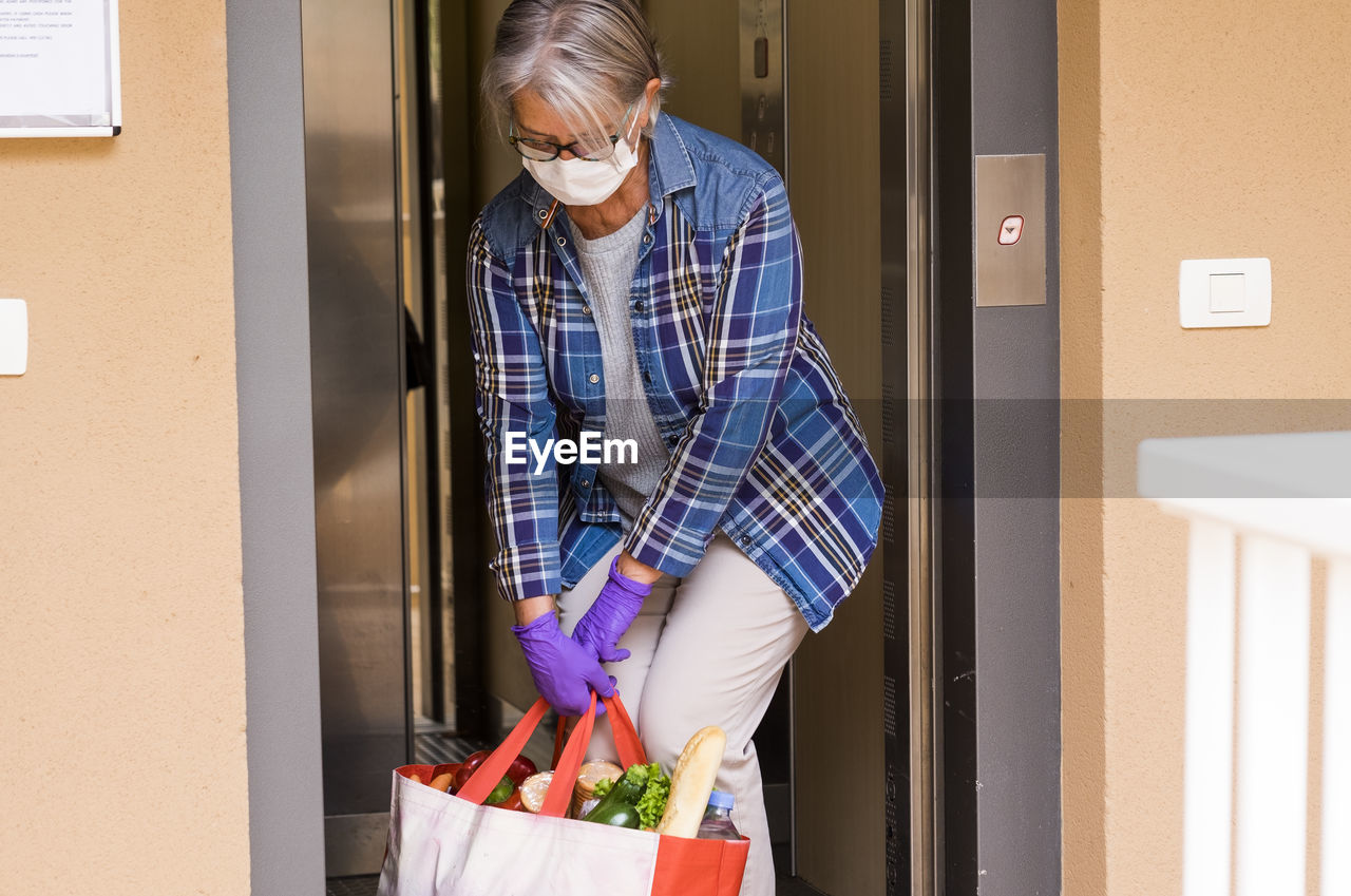 Senior woman wearing mask holding food in bag standing by elevator