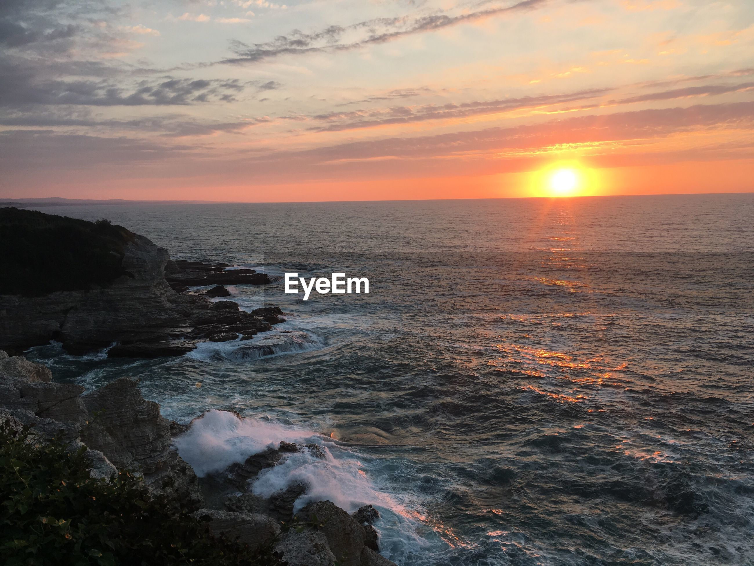 sunset, sea, water, scenics, horizon over water, beauty in nature, sun, tranquil scene, nature, beach, idyllic, sky, tranquility, reflection, cloud - sky, shore, orange color, outdoors, majestic, non-urban scene, coastline, remote, bright, wave, rock formation, no people, vacations, seascape, tourism