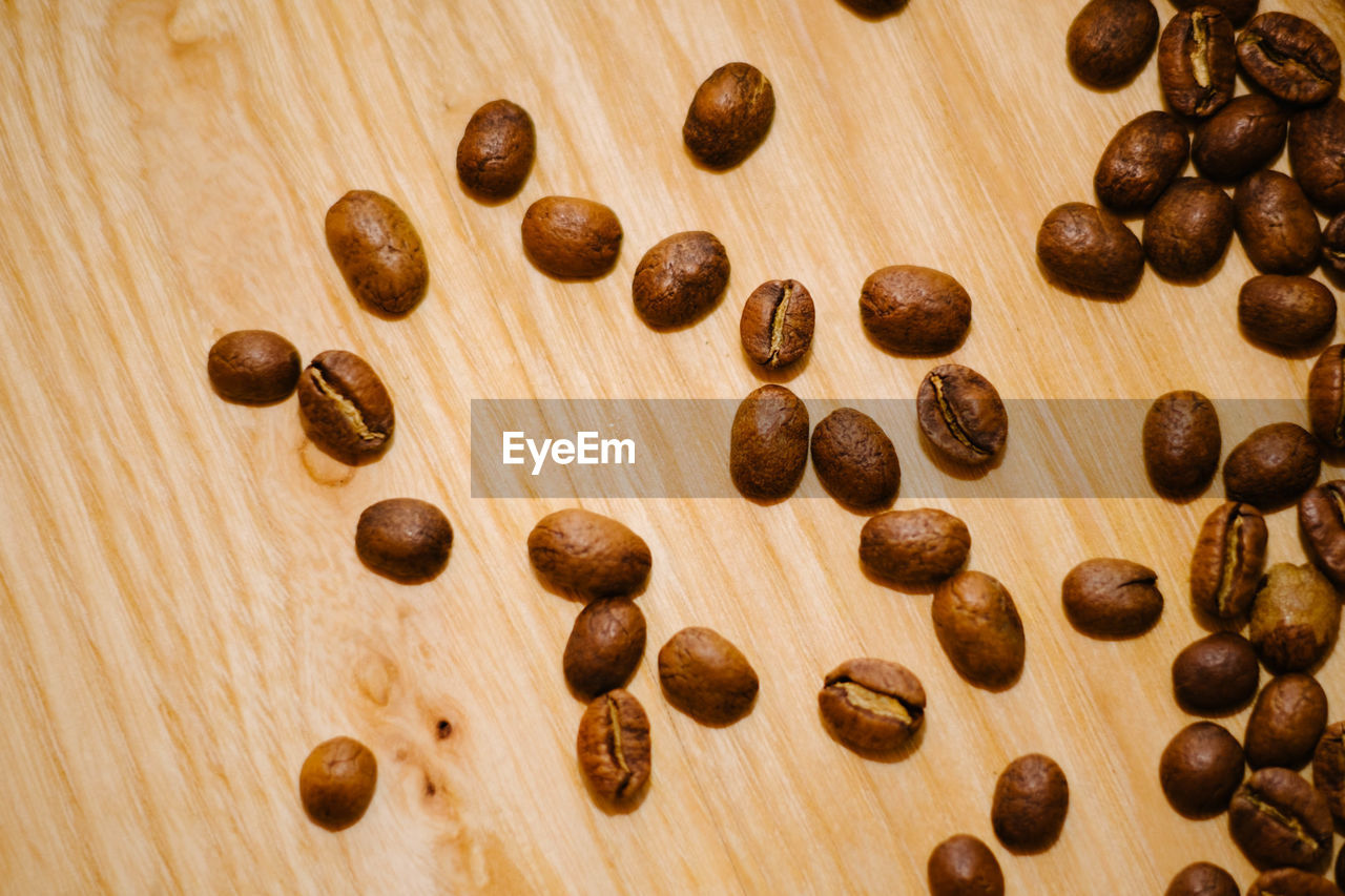 HIGH ANGLE VIEW OF COFFEE BEANS ON WOODEN TABLE