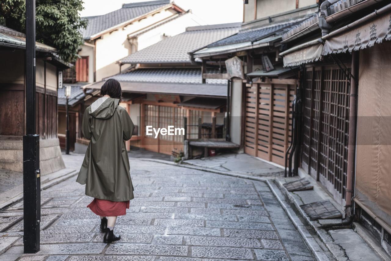 Rear View Of Woman Wearing Raincoat Walking On Street Amidst Buildings