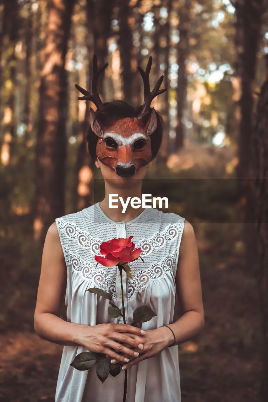 Close-Up Of Woman Holding Rose While Wearing Mask In Forest