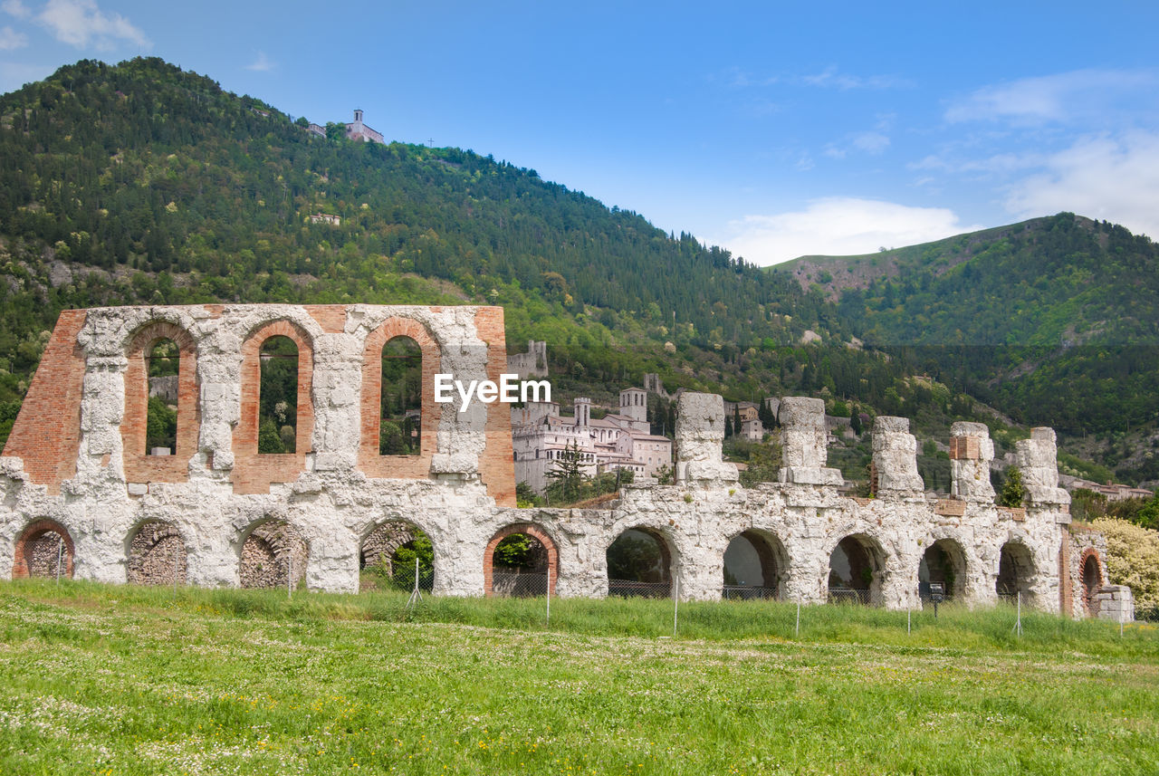 plant, history, the past, architecture, built structure, sky, tree, grass, ancient, green color, nature, old ruin, mountain, day, arch, building exterior, no people, land, ancient civilization, old, outdoors, archaeology, ruined, deterioration
