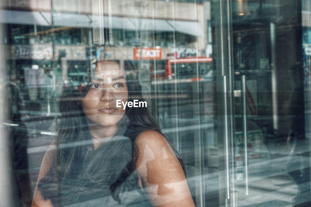 Woman looking through glass window
