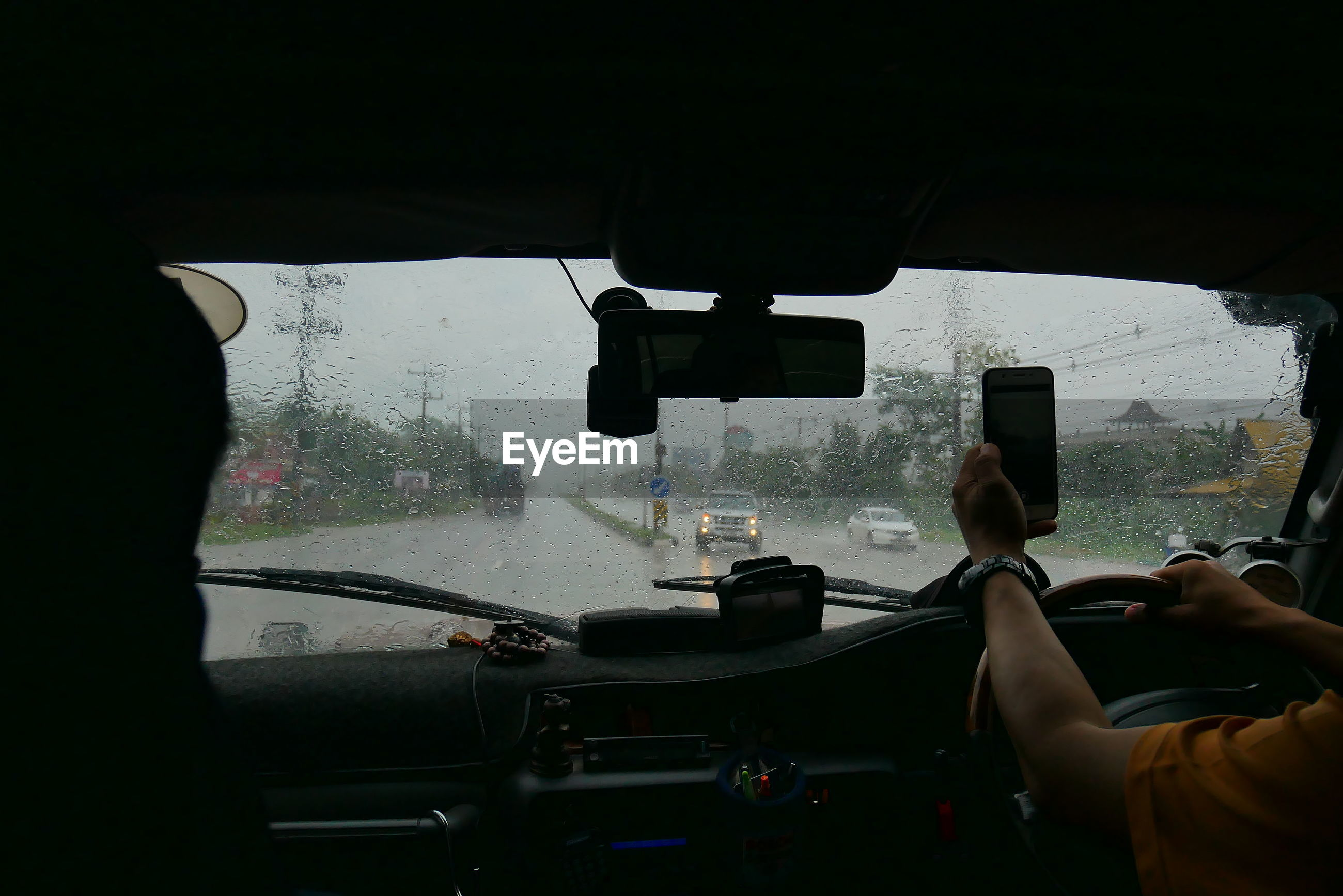 Midsection of man using phone while driving car during rainy season