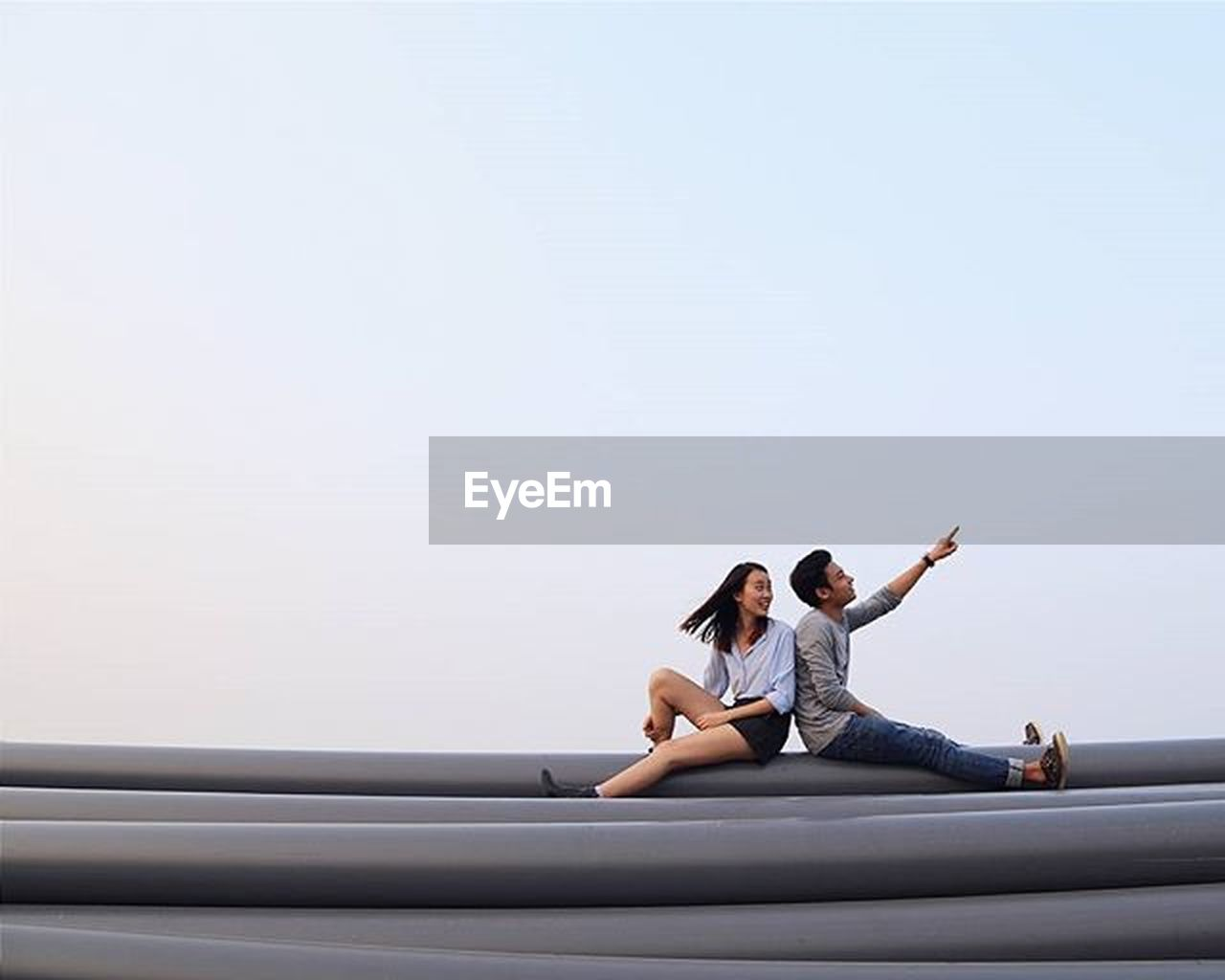 two people, relaxation, adults only, adult, copy space, wireless technology, sitting, full length, day, connection, casual clothing, togetherness, men, women, people, sky, couple - relationship, smiling, technology, outdoors, happiness, beautiful people, young adult, beautiful woman, young women, friendship, nature