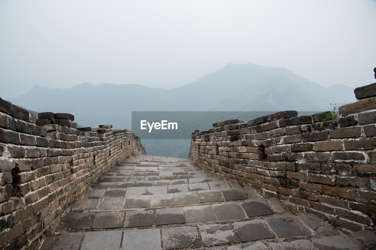mountain, architecture, sky, built structure, history, the past, fog, travel destinations, ancient, wall, mountain range, tourism, travel, ancient civilization, no people, nature, the way forward, scenics - nature, building exterior, stone wall, outdoors, brick
