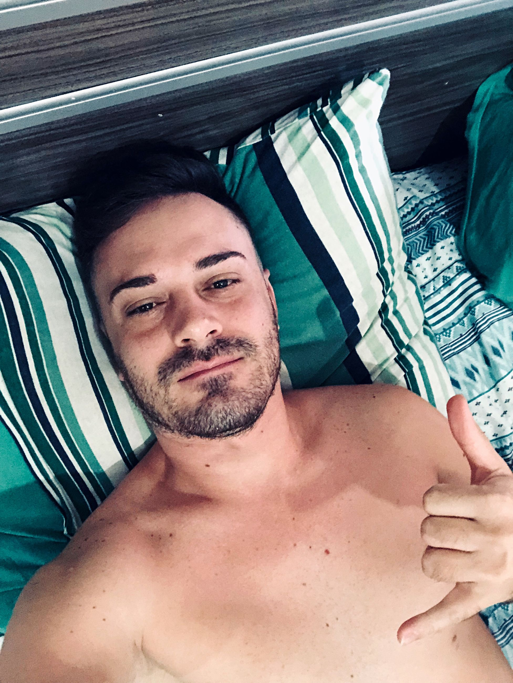 High angle view of shirtless man gesturing horn sign while lying on bed