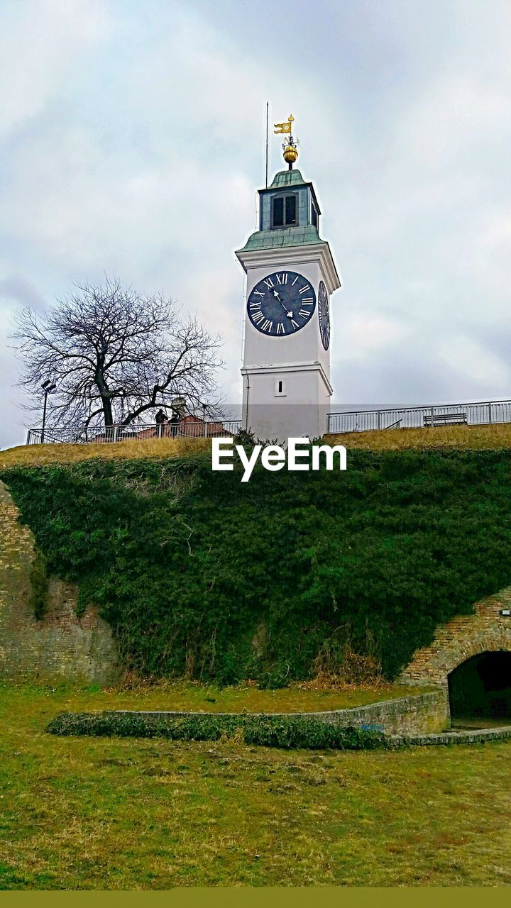 cloud - sky, sky, architecture, grass, tower, built structure, green color, tree, no people, building exterior, day, clock tower, bell tower, nature, outdoors, lighthouse, water, clock, beauty in nature, time