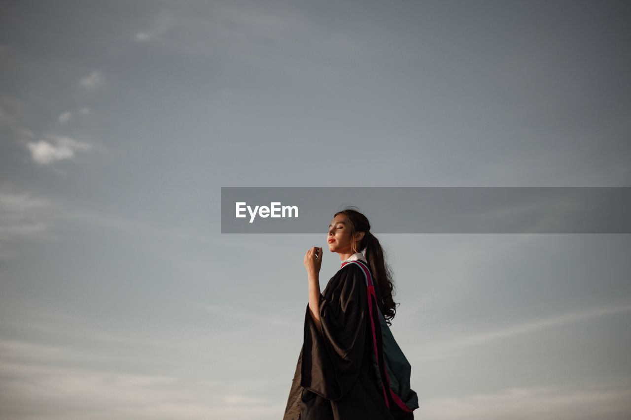 LOW ANGLE VIEW OF YOUNG WOMAN LOOKING AGAINST SKY