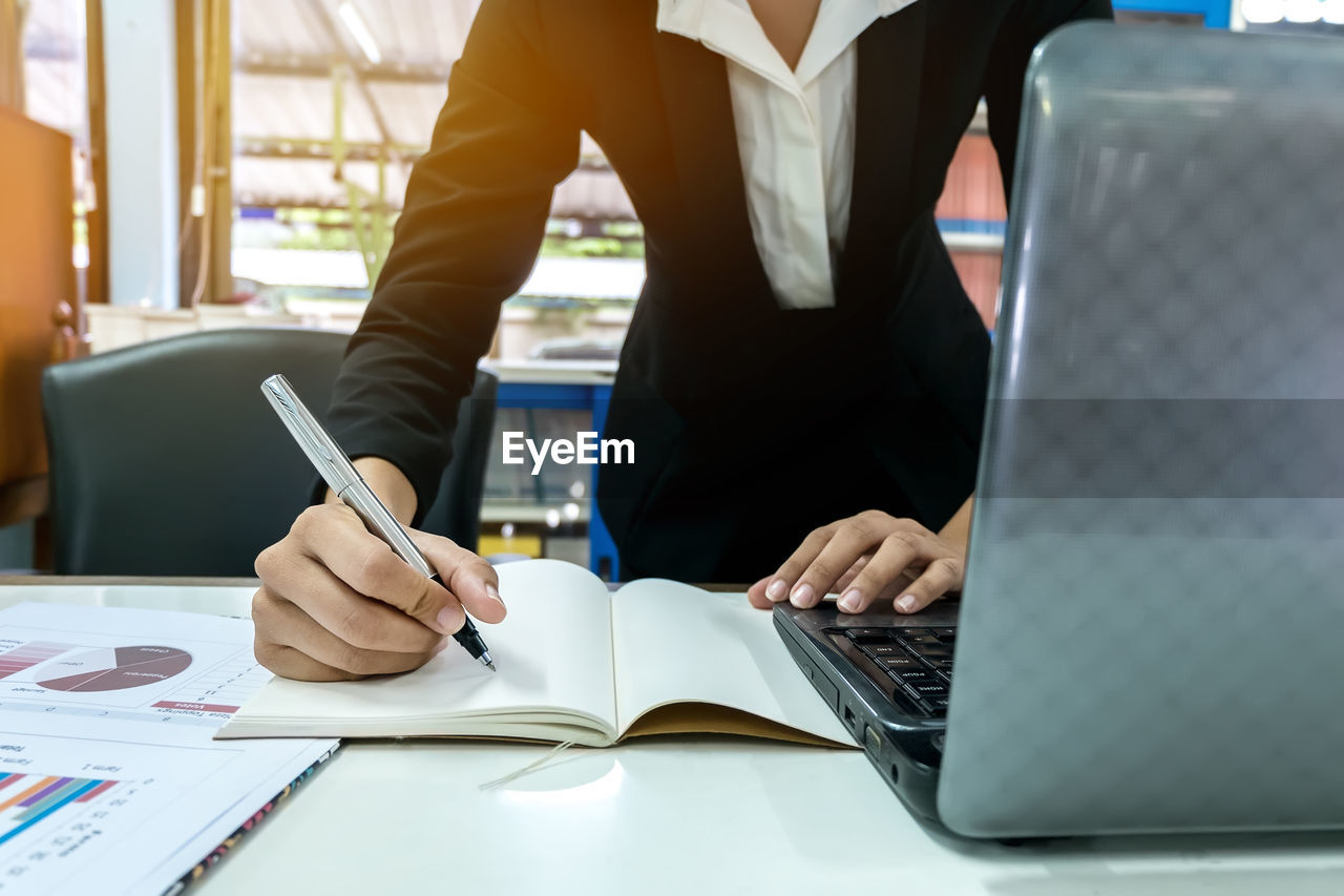 Midsection of woman writing in book by laptop and chart at office desk