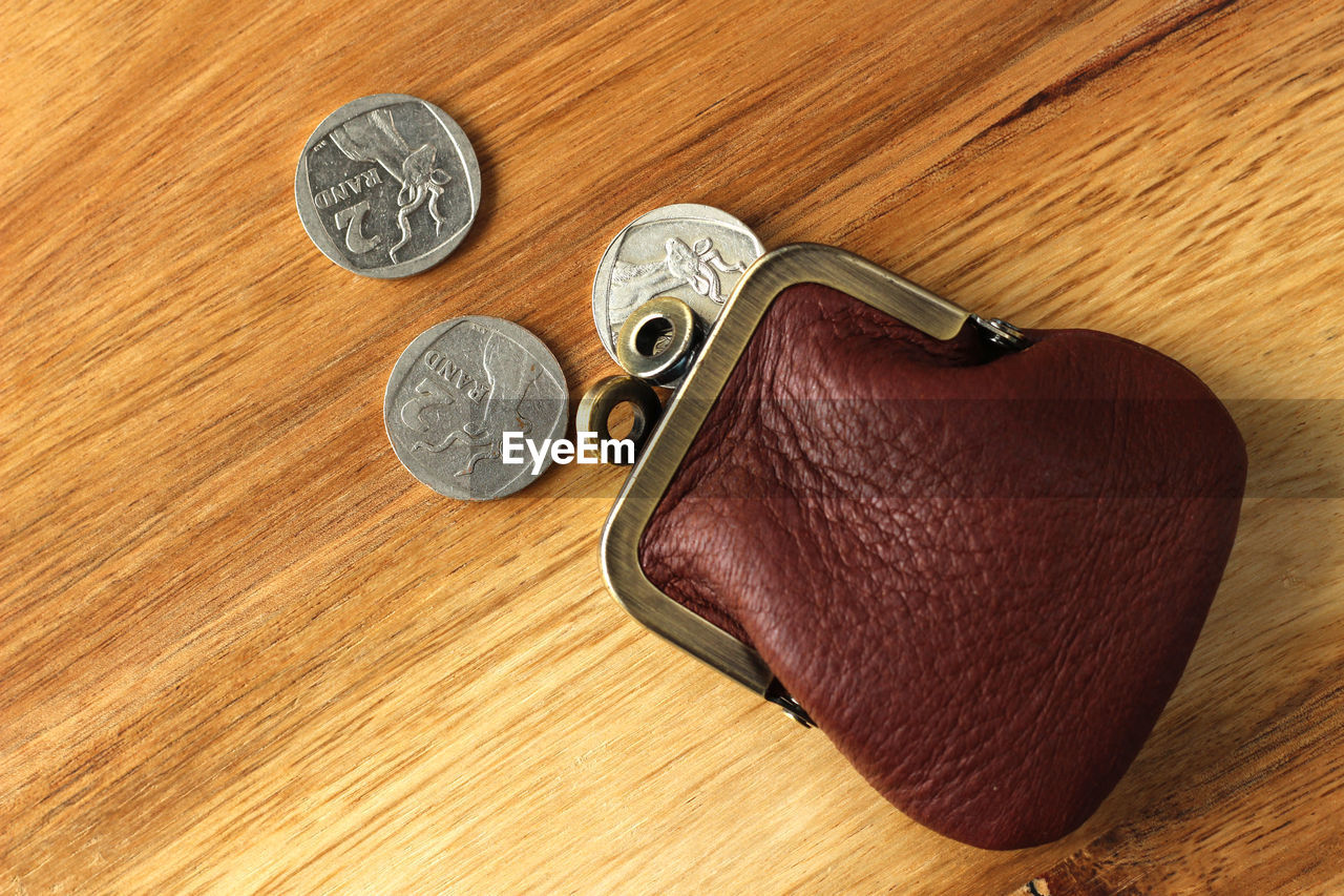 Close-up of coins spilling from wallet
