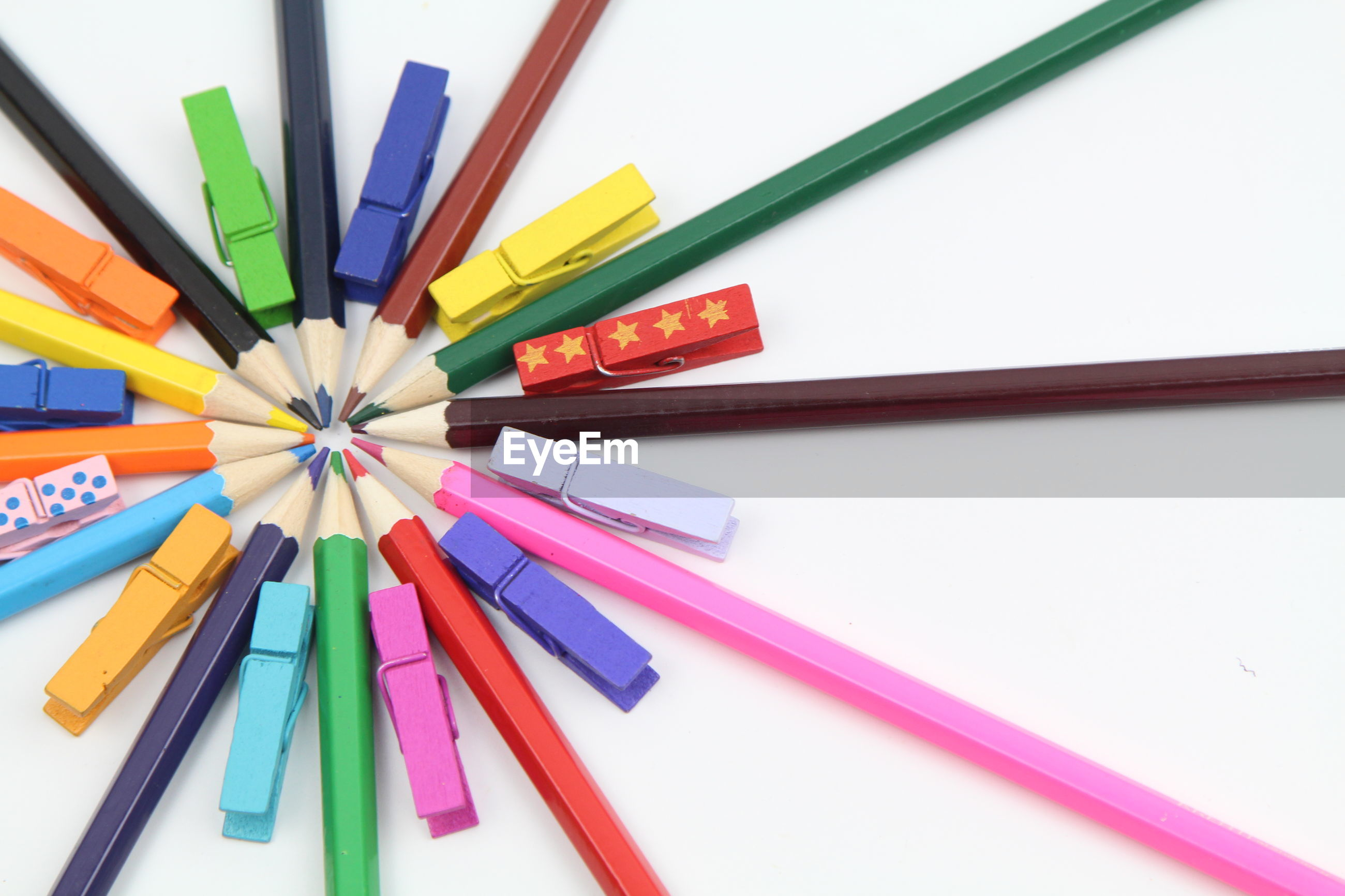Close-up of colored pencils with colorful clothespins on white background