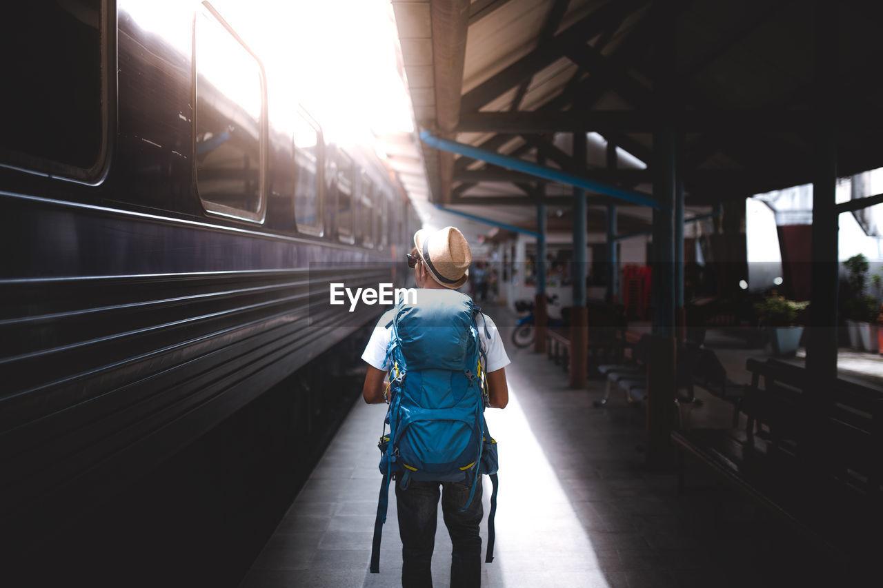 Rear view of man standing at railroad station platform