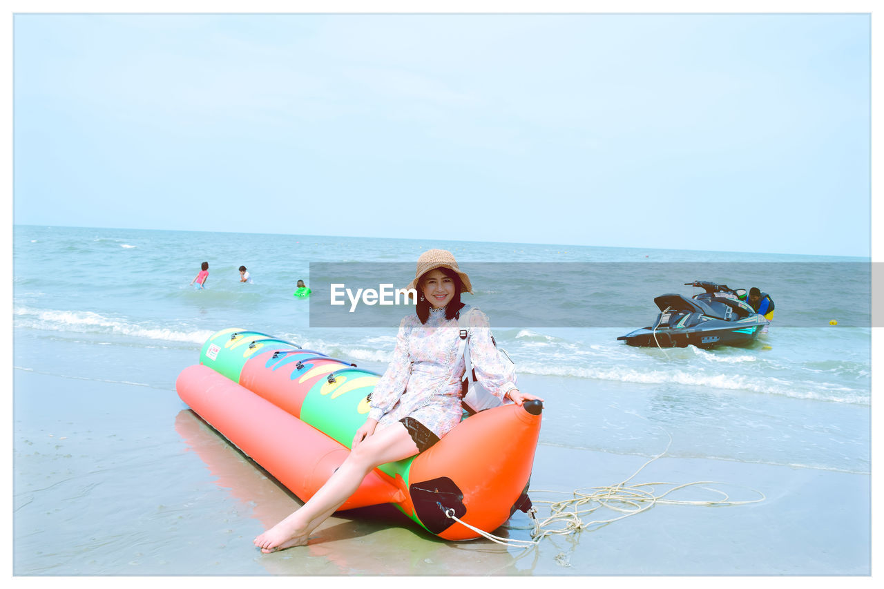 water, sea, horizon over water, horizon, beach, sky, real people, leisure activity, transfer print, land, lifestyles, auto post production filter, full length, one person, nature, vacations, sitting, trip, inflatable, outdoors