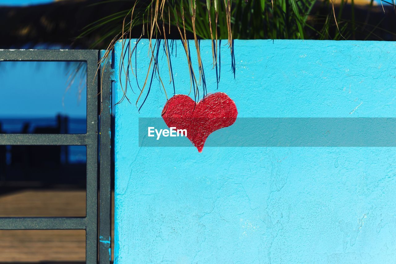 heart shape, love, positive emotion, emotion, blue, red, close-up, no people, day, outdoors, creativity, art and craft, focus on foreground, wall - building feature, nature, wood - material, design, shape, built structure, valentine's day - holiday, turquoise colored