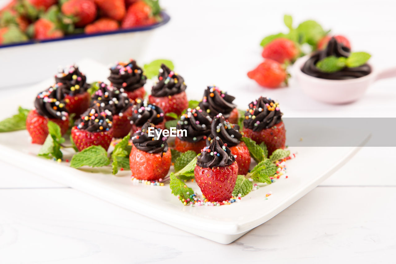 food, food and drink, freshness, berry fruit, still life, healthy eating, fruit, ready-to-eat, plate, table, indoors, strawberry, close-up, indulgence, wellbeing, no people, focus on foreground, serving size, selective focus, sweet food, temptation, mint leaf - culinary, snack