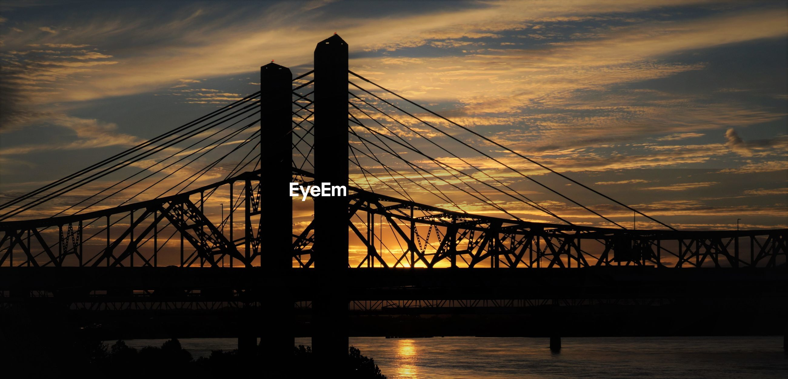 Silhouette bridge against sky at sunset