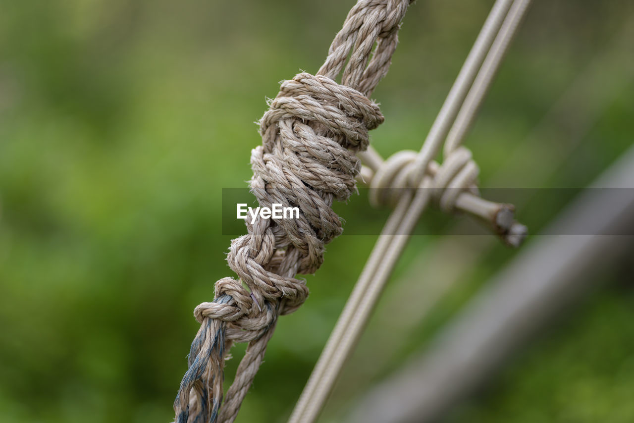 CLOSE-UP OF ROPES TIED ON WOODEN POST