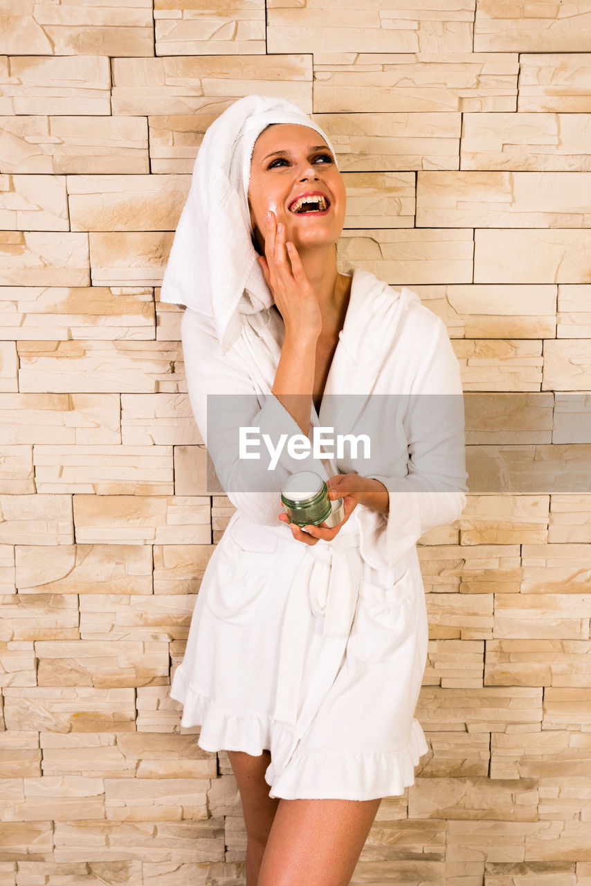 Beautiful Happy Woman In Bathrobe Applying Moisturizer On Face Against Wall